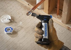 Gloved hand holding butane torch in home workshop